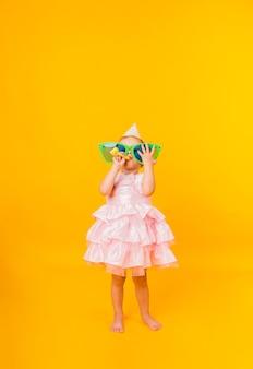 Маленькая девочка в розовом пышном платье на желтом фоне