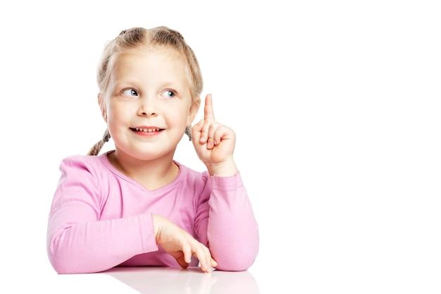 ピンクのセーターを着た少女がテーブルに座って、人差し指を上げました。白い壁に分離されました。テキスト用のスペース。