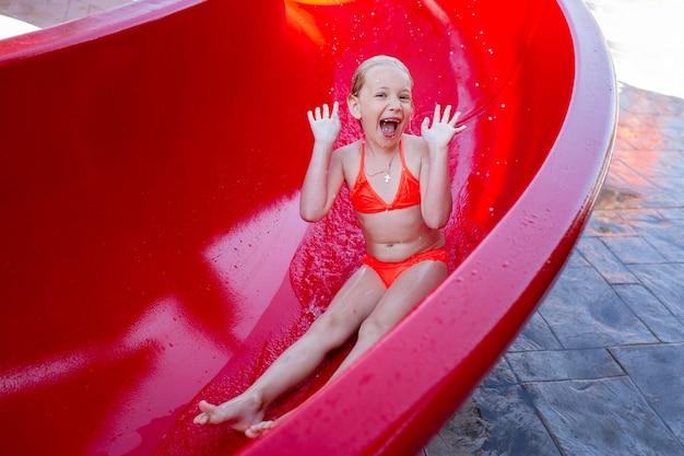 분홍색 수영복을 입은 어린 소녀가 여름 방학 동안 워터 파크에서 워터 슬라이드를 미끄러 져 내려갑니다.