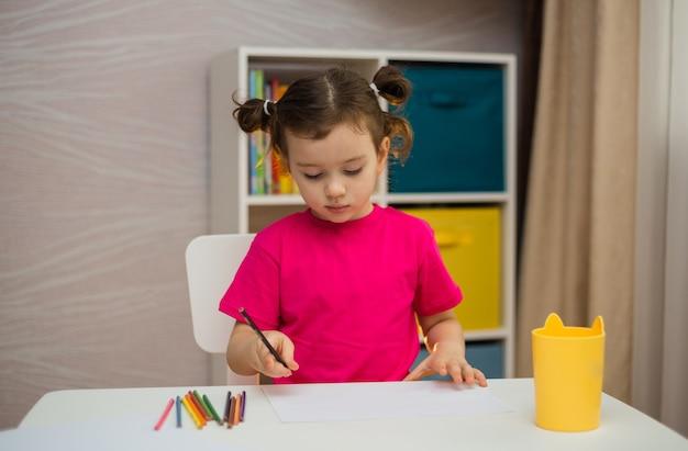 분홍색 티셔츠를 입은 어린 소녀가 방의 테이블에서 종이에 연필로 그립니다.