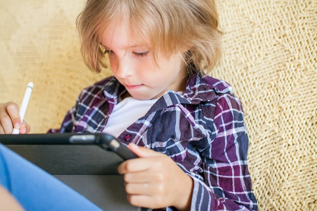격자 무늬 셔츠를 입은 어린 소녀가 태블릿 온라인 학습 개념에 집중하여 그림을 그립니다.