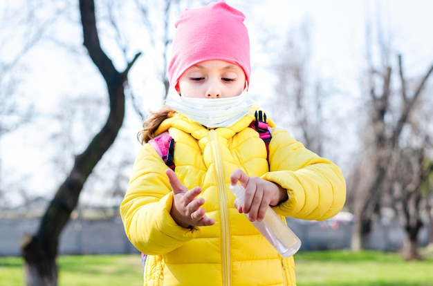 防護マスクの少女は、手の消毒剤を手に持っています。