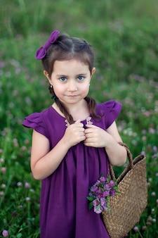 花畑に紫色のドレスを着た少女が立っている