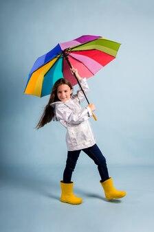 Маленькая девочка в плаще и желтых резиновых сапогах стоит и держит разноцветный зонтик на синем фоне с местом для текста