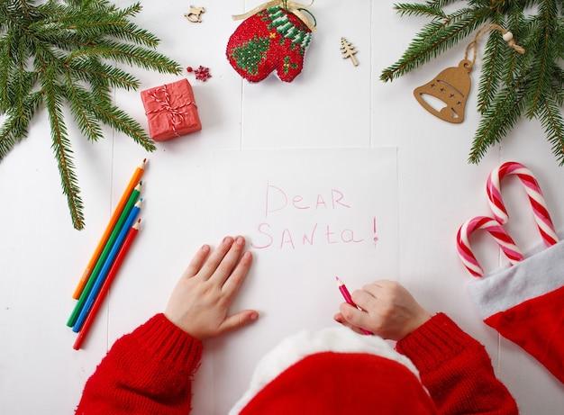 Маленькая девочка в красной новогодней шапке пишет письмо деду морозу.