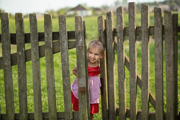 Маленькая девочка в красном платье выглядывает из-за деревянного забора.