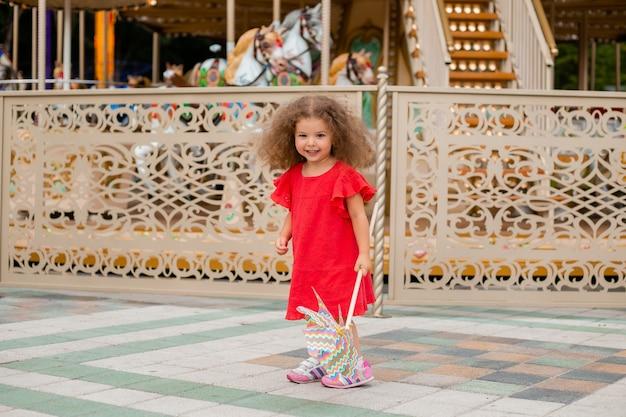 Маленькая девочка в красном платье бегает и развлекается возле карусели в парке развлечений
