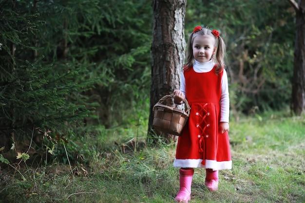 Маленькая девочка в красной шляпе и платьях гуляет по парку. косплей на сказочного героя