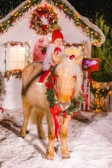 Маленькая девочка в красной шляпе сидит на красном пони в новогодней шапке и венке