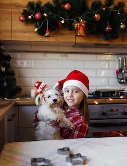 赤いサンタの帽子をかぶった少女は、クリスマスライトで飾られたキッチンで、自宅のペットの犬を抱きしめます。クリスマスを待っています。