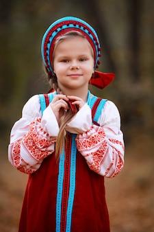 Маленькая девочка в красном сарафане стоит в осеннем лесу и заплетает волосы