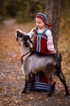 Маленькая девочка в красном сарафане стоит рядом с черным козленком в осеннем лесу