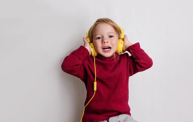 Маленькая девочка в красном свитере слушает музыку в наушниках и смеется на белом фоне.