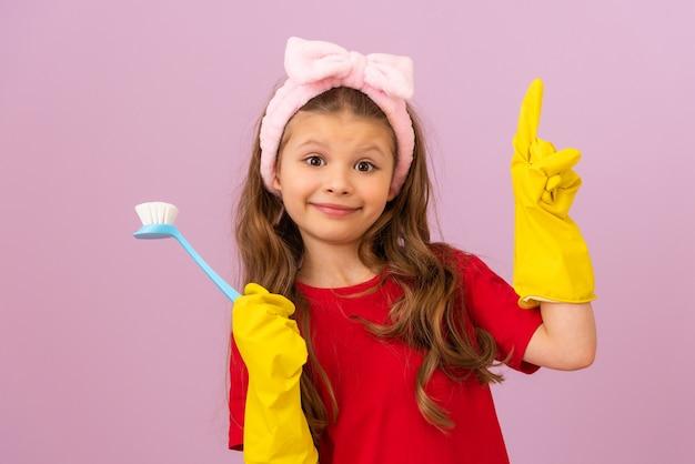 빨간 티셔츠와 고무 장갑을 입은 어린 소녀가 청소용 브러시를 들고 있습니다.