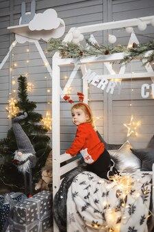 赤い暖かいセーターを着た少女が、おもちゃやプレゼントを持ってクリスマスツリーの近くのベッドに座っています。幸せな子供時代。年末年始の雰囲気
