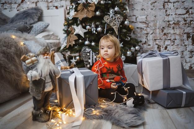 Маленькая девочка в красном теплом свитере сидит под елкой с игрушками и подарками. счастливое детство. атмосфера новогоднего праздника