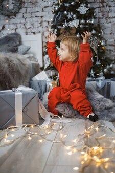 빨간 따뜻한 스웨터를 입은 어린 소녀가 장난감과 선물이 있는 크리스마스 트리 아래에 앉아 있습니다. 행복한 어린 시절. 연말연시 분위기