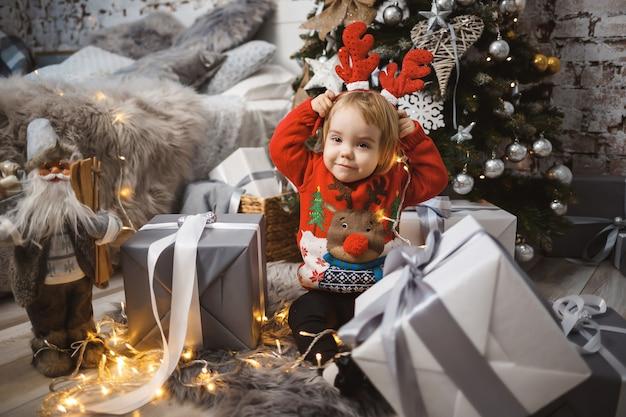 빨간 따뜻한 스웨터를 입은 어린 소녀가 머리에 뿔이 달린 장난감과 선물을 들고 크리스마스 트리 아래에 앉아 있습니다. 행복한 어린 시절. 연말연시 분위기