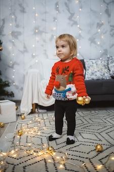 빨간 따뜻한 스웨터를 입은 어린 소녀가 장난감과 선물이 있는 크리스마스 트리 근처에 서 있습니다. 행복한 어린 시절. 연말연시 분위기