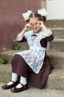 Маленькая девочка в школьной форме играет с закусками