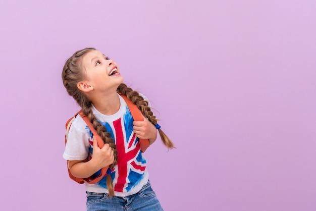 영국 국기와 배낭이 달린 셔츠를 입은 어린 소녀가 귀하의 광고를 봅니다.