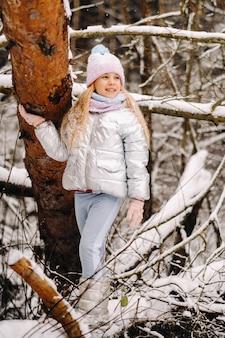 冬に銀のジャケットを着た少女が冬に外に出る