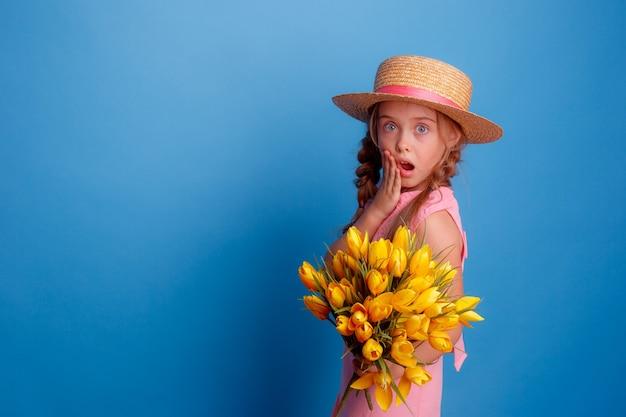 麦わら帽子の少女は青い背景に黄色いチューリップの花束を持っています