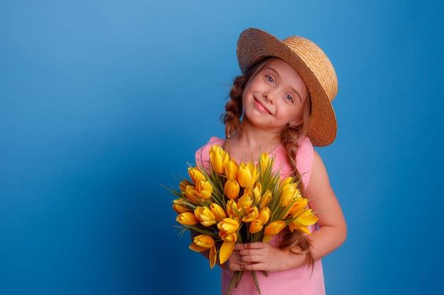 麦わら帽子の少女は黄色いチューリップの花束を持っています