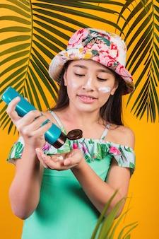 日焼け止めを着ている水着と帽子の少女。