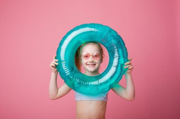 Маленькая девочка в купальнике с плавательным кругом на розовом фоне