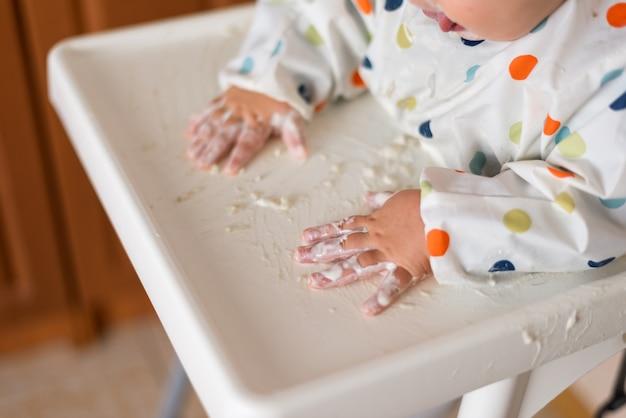 Маленькая девочка в футболке и тарелке сидит в детском кресле, ест руками каши с йогуртовой пищей