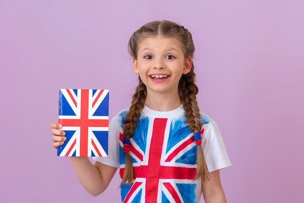 Tシャツを着た少女が英語を学んでいます。