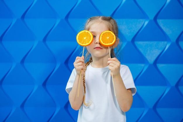 티셔츠를 입은 어린 소녀는 미소를 지으며 파란색 배경에 그녀의 눈 앞에 주황색 과일 두 개를 들고 있습니다. 개념: 봄철 avitomnosis와의 싸움.