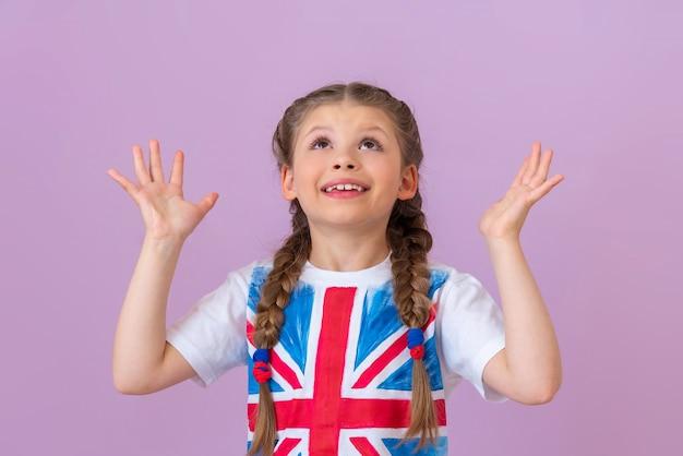 Маленькая девочка в футболке с изображением флага великобритании подняла руки вверх.