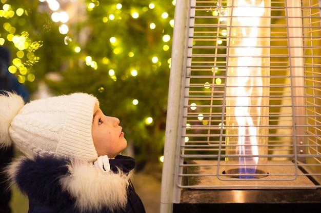 따뜻한 모자에있는 어린 소녀가 도시의 크리스마스 시장에서 온난화되는 가스 버너의 불꽃을 봅니다.