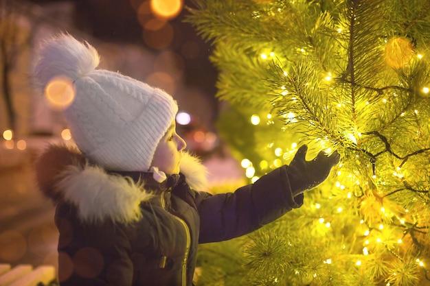따뜻한 모자에있는 어린 소녀가 거리의 크리스마스 트리에있는 화환의 황금빛을 봅니다.