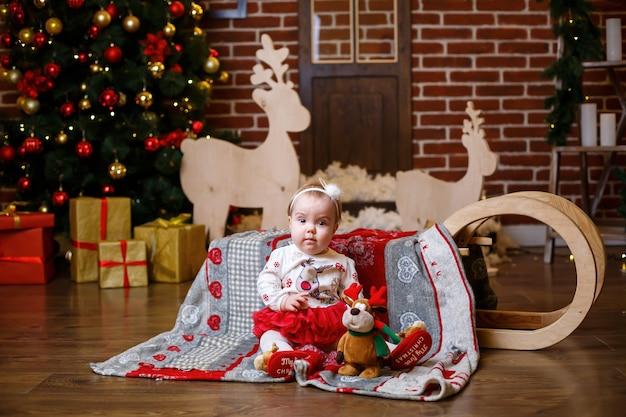 따뜻한 스웨터를 입은 어린 소녀가 장난감과 선물이 있는 크리스마스 트리와 함께 서 있습니다. 행복한 어린 시절 새해 축제 분위기