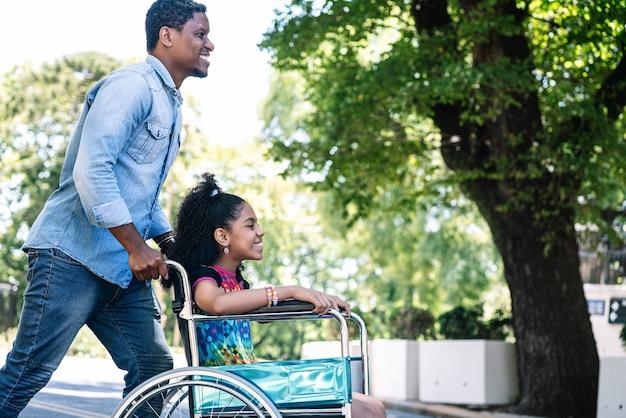 屋外で一緒に散歩しながら父親と一緒に楽しんで楽しんでいる車椅子の少女
