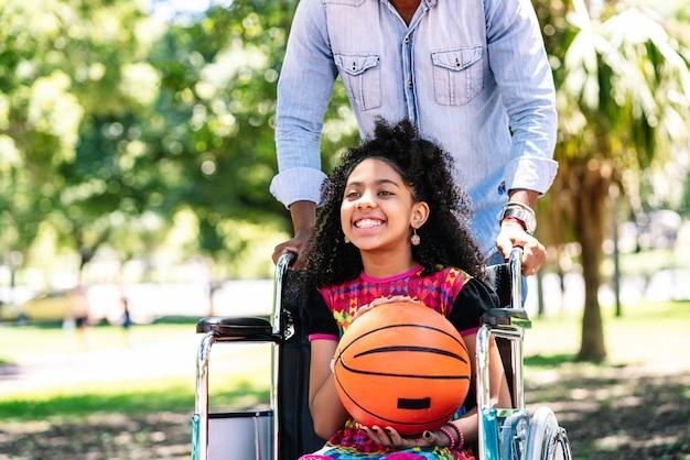公園で一緒にバスケットボールをしながら父親と一緒に楽しんでいる車椅子の少女