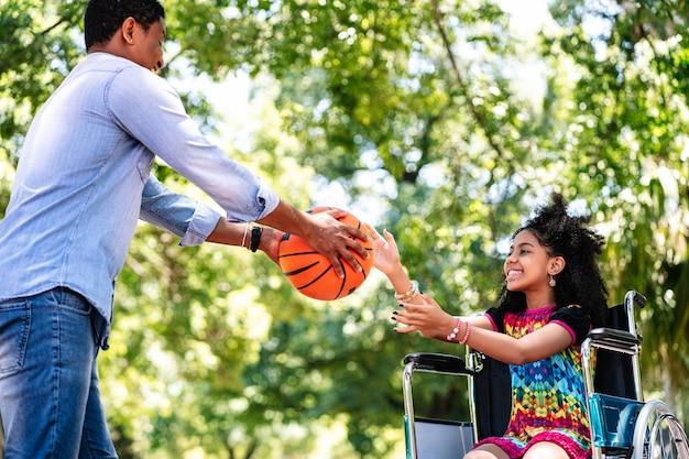 公園で一緒にバスケットボールをしている間、彼女の父と楽しんでいる車椅子の少女。