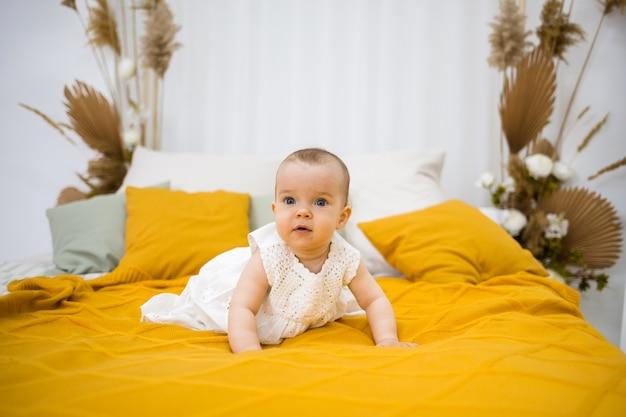 흰색면 드레스를 입은 어린 소녀가 노란색 침대보가있는 침대에서 기어 다닙니다.