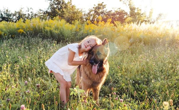 흰 드레스를 입은 어린 소녀가 푸른 잔디 위에 서있는 큰 독일 셰퍼드 개를 안고 있습니다. 강아지와 함께하는 어린이 게임.
