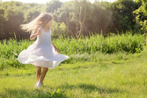 흰 드레스를 입은 어린 소녀가 강가의 풀밭에서 춤을 추고 있습니다.