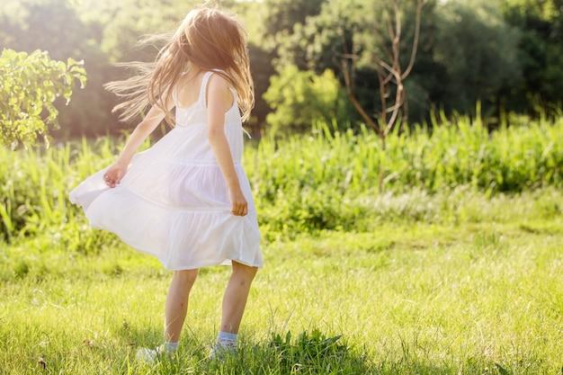 하얀 드레스를 입은 어린 소녀가 강 잔디 위에서 춤을 추고 있다