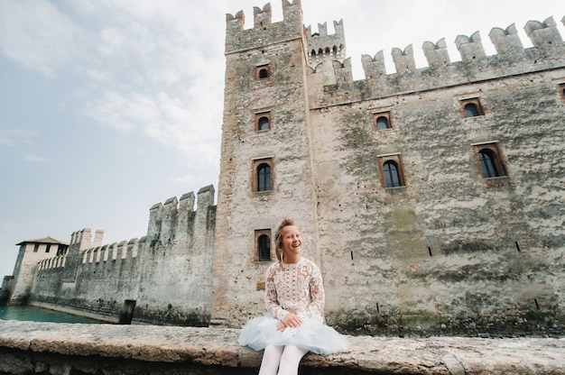シルミオーネの街の古い城の背景に白いドレスを着た少女