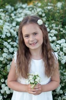 Маленькая девочка в белом платье стоит с букетом белых цветов. период цветения.