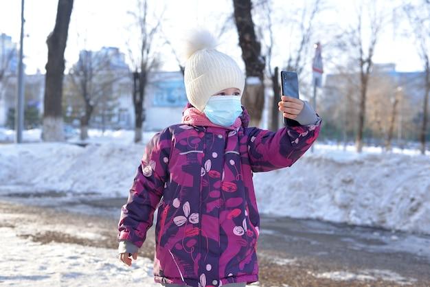 白い帽子と暖かいジャケットとマスクを着た小さな女の子が冬に外で電話を使って話している。リモート通信の概念。