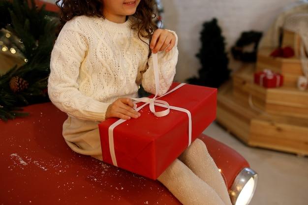 흰 스웨터를 입은 어린 소녀가 흰 리본이 달린 빨간 선물 상자를 엽니다