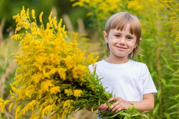 Маленькая девочка в белой футболке и желтых джинсах стоит на цветочном поле, держит в руках букет желтых осенних цветов и улыбается.