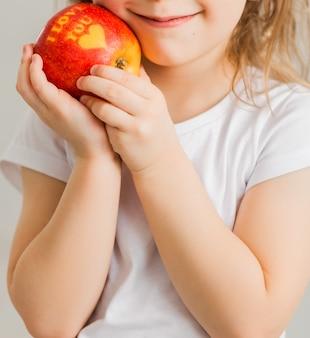 흰색 티셔츠를 입은 어린 소녀는 내가 당신을 사랑한다는 비문과 함께 그녀의 손에 사과를 들고 있습니다. 세로 사진
